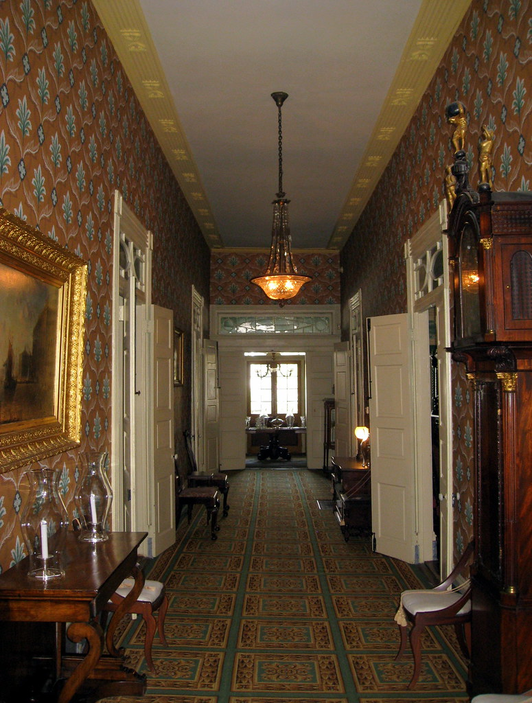 Interior hallway of the Beauregard Keyes House, looking down a red hallway decorated with various ornaments.