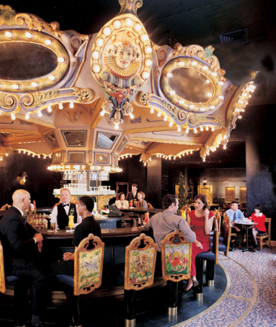Patrons drinking under a lit ornament at the Carousel Bar in the Hotel Monteleone.