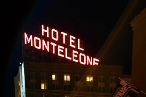 A red neon sign, which reads Hotel Monteleone lights up the night sky.