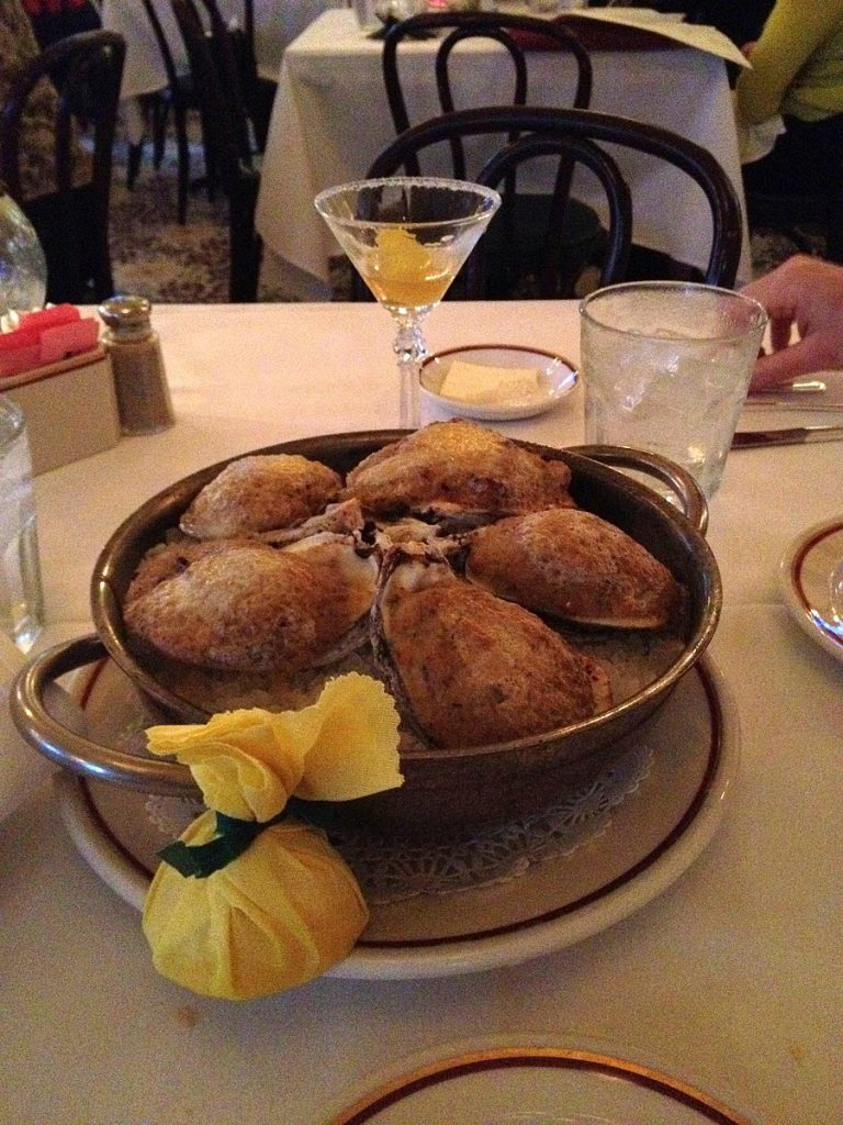 Plate of oysters bienville with a side of lemon