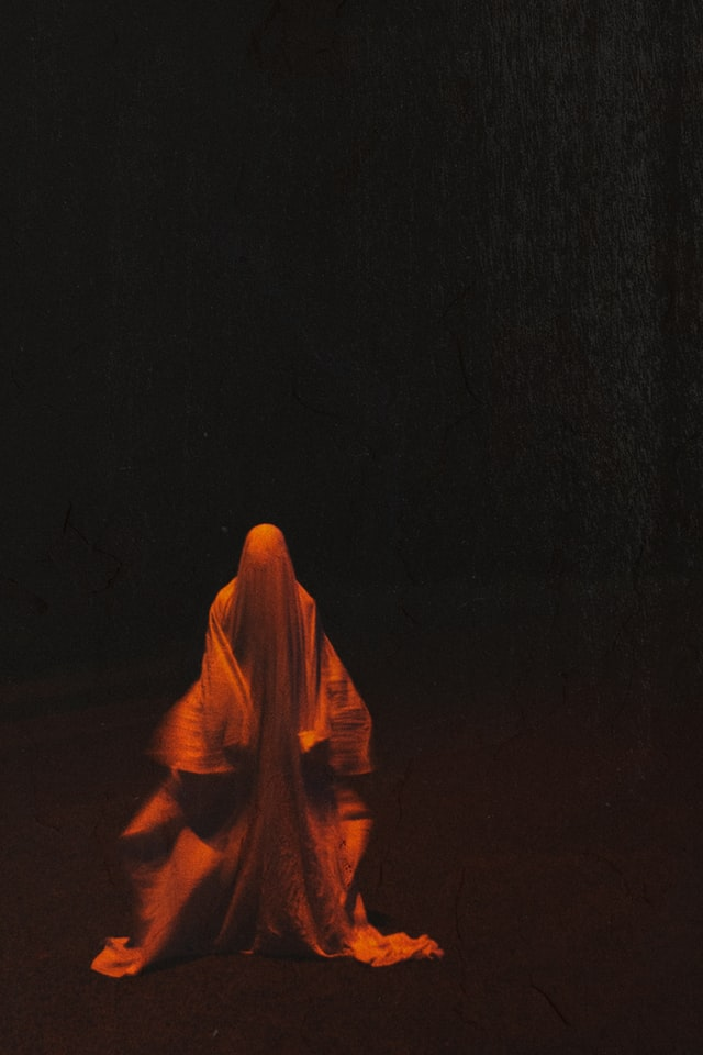 Ghost covered by red sheet against a black background